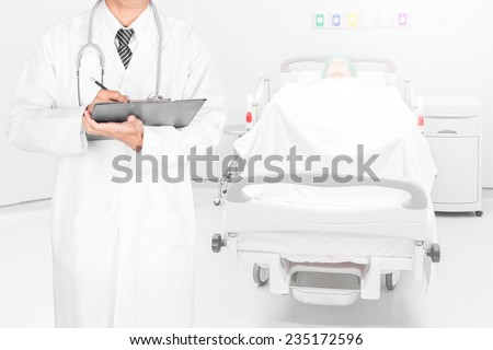 Doctor writing on a folder of diagnosis result in patient room - stock photo