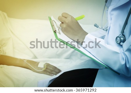 doctor writing on a medical chart with patient lying in a hospital bed focus on hand. - stock photo