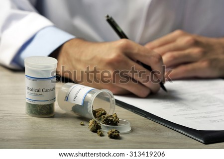 Doctor writing on prescription blank and bottle with medical cannabis on table close up - stock photo