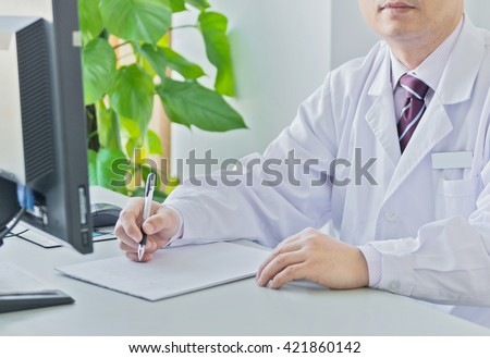 Doctor writing something in the office - stock photo