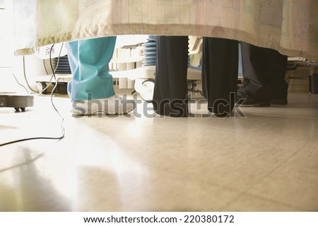 Doctors and nurses feet under curtain - stock photo