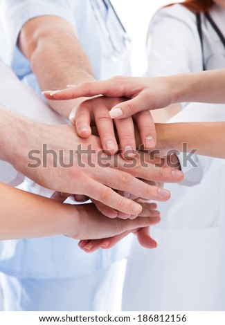 Doctors and nurses in a medical team stacking hands in a show of cooperation and solidarity isolated on white