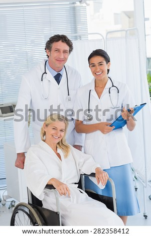 Doctors and patient in wheelchair smiling at camera in hospital - stock photo