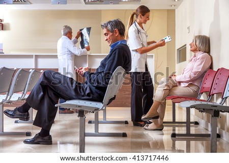 Doctors and patients in hospital room discussing exam results. - stock photo
