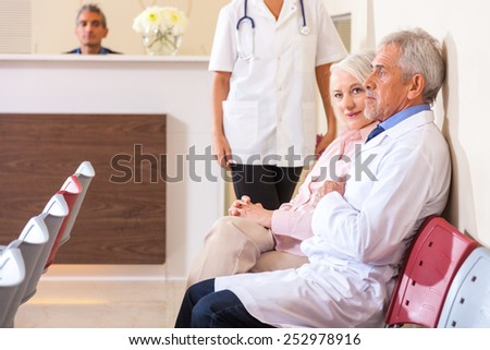 Doctors and patients in hospital waiting room. - stock photo