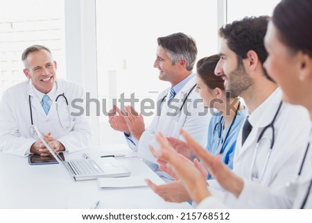 Doctors applauding a fellow doctor for his speech