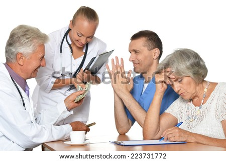 Doctors at the table on white background exemining xray - stock photo