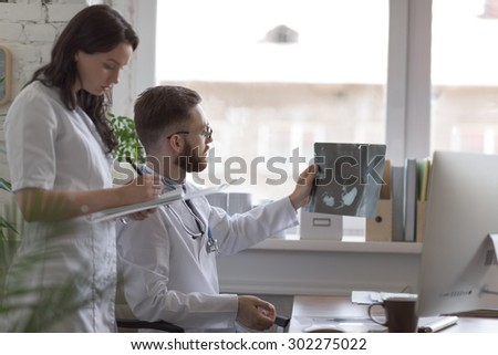 Doctors discussing intestines xray at medical office