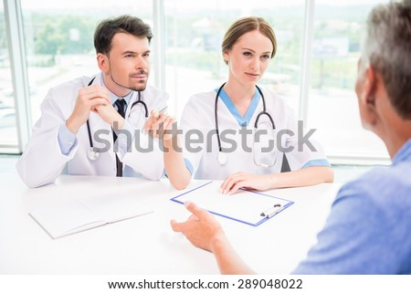 Doctors explaining diagnosis to mature male patient in hospital.
