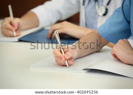doctors hands writing at table closeup