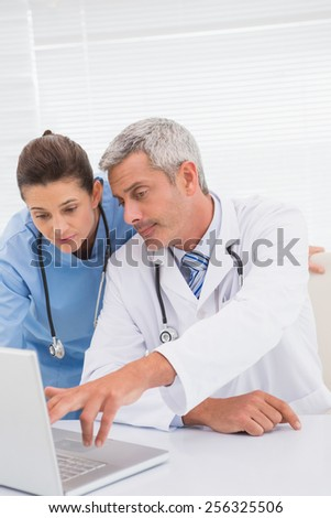 Doctors looking at laptop in medical office