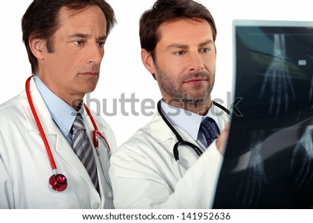 Doctors looking at X-ray - stock photo