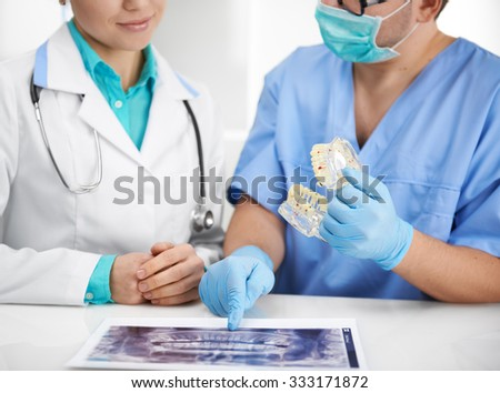 Doctors meeting in lab. Two dental specialists discussing teeth disease and treatment sitting at the desk with jaw model and X-ray.  - stock photo