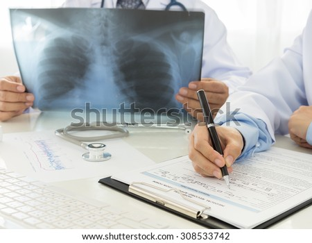 Doctors records data and looking film X-Ray in office of hospital. - stock photo