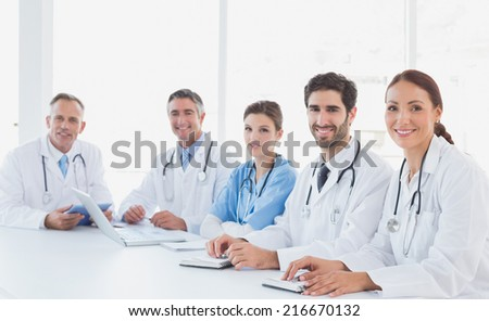 Doctors smiling at the camera as they all sit - stock photo