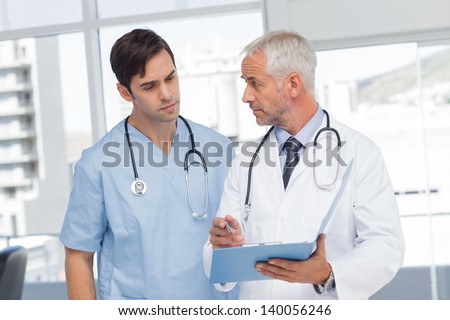 Doctors talking about a file in hospital - stock photo