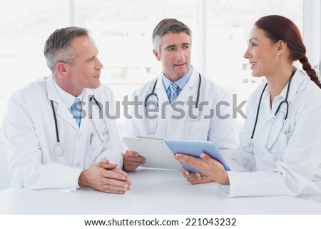 Doctors using a tablet together while sitting