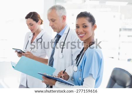 Doctors working together on patients file in medical office - stock photo