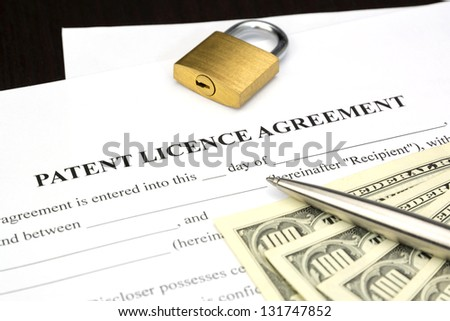 Document Form of patent licence agreement with lock and dollar money - stock photo
