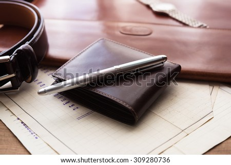 Documents, pen, belt and a wallet on a wooden desk. hotel table or gentleman's desk. shallow depth of field. - stock photo