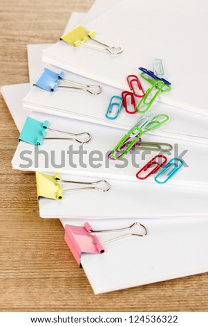 Documents with binder clips on wooden table - stock photo
