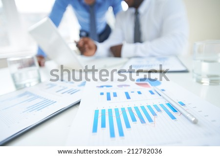 Documents with chart and graph and pen on background of two employees working - stock photo