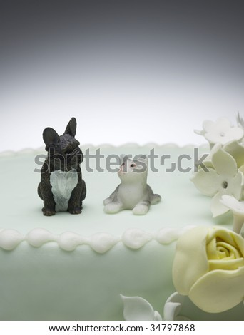 Dog and cat figurines on top of wedding cake - stock photo