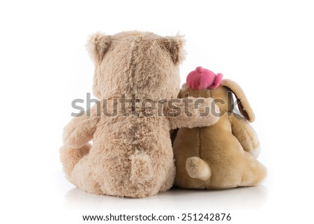 Dog and teddy bear with their arms around each other. - stock photo