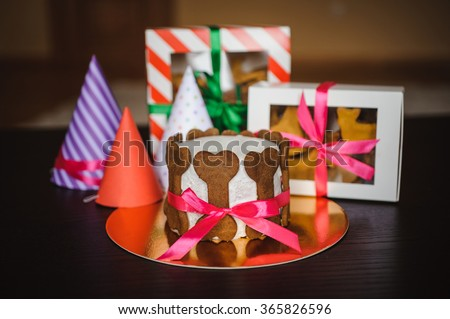 dog cake and cookie in boxes with ribbons and birthday hats - stock photo
