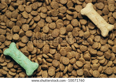 Dog food background with two bone shaped treats placed on top - stock photo