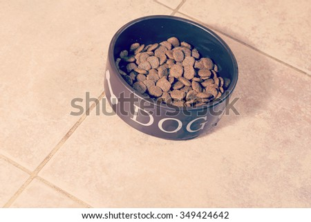Dog food in a food bowl for dogs. The cup is on the kitchen floor. Image has a vintage effect applied. - stock photo