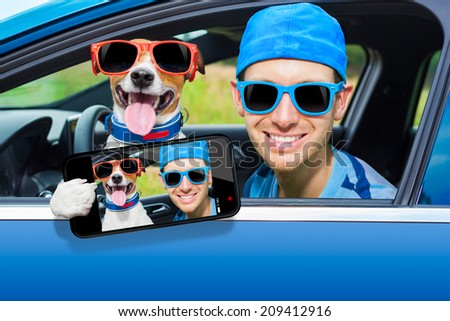 dog in a car looking through window with Driving instructor taking a selfie - stock photo