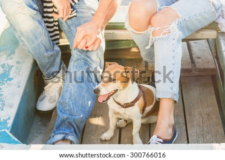 dog in a wooden boat on the background of couples in love