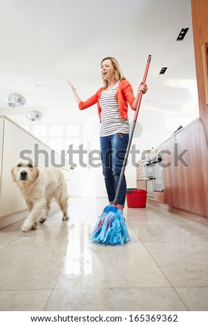 Dog Making Mess Of Newly Mopped Floor - stock photo
