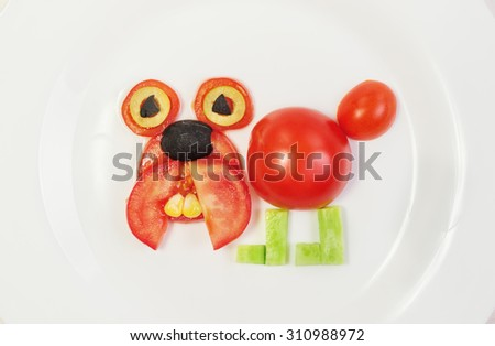 Dog of fresh tomatoes, cucumbers, corn and olives on a plate. The concept of children's breakfast, healthy diet, raw food diet, lose weight, vegetarian, vegan, slimming. Funny animals from vegetables. - stock photo