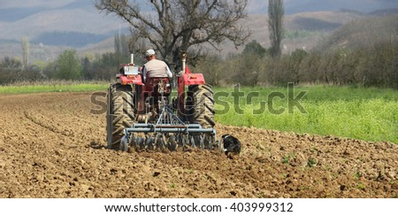 dog on the field and  man in tractor plowing field in spring - stock photo