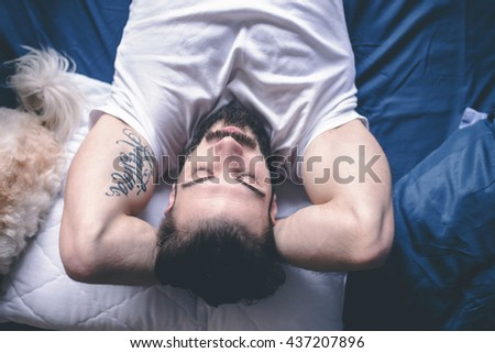 Dog owner in bed with his cute puppy sleeping - stock photo