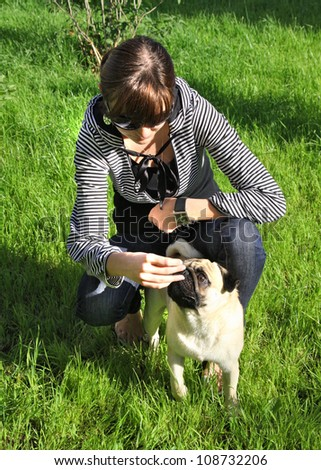 Dog  Pug and young woman on green grass in a park - stock photo
