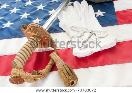 dog tags on military gloves by sword - stock photo