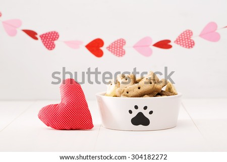 Dog treats on a white bowl with a heart cushion with a garland of hearts - stock photo