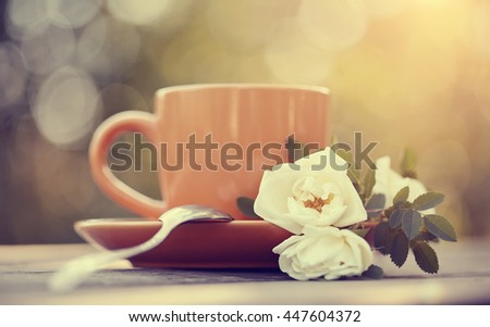 Dogrose and red cup with a spoon on a table. - stock photo
