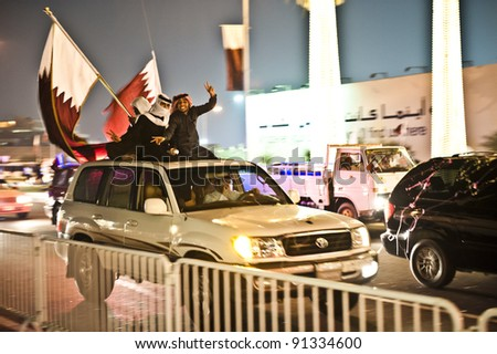 DOHA-DEC 18: Qataris with flags sit or stand on a vehicle during a parade to celebrate their National Day, on December 18, 2011 in Doha, Qatar.  This has been an annual event since 2009. - stock photo