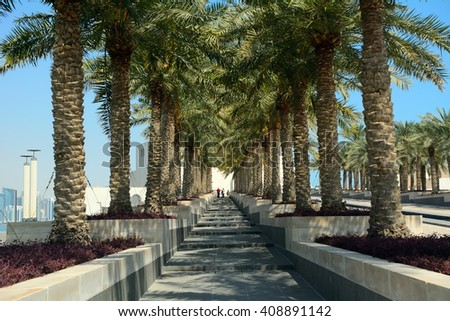DOHA - MARCH 2 : Palmtrees in front of the Museum of the Islamic Arts at 2 March, 2015 in Doha, Qatar. Doha is a blended mix of modern architecture and green nature. - stock photo