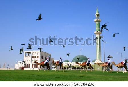 DOHA, QATAR - 01 APRIL 2010: Traditional arabs riding camels in front of the Grand Mosque on 1st April 2013 in Doha, Qatar