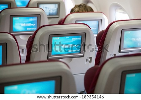 DOHA, QATAR - FEBRUARY 18, 2014: Economy class seats with entertainment system onboard. Qatar Airways Economy Class was named best in the world in the 2009 and 2010 Skytrax Awards. - stock photo