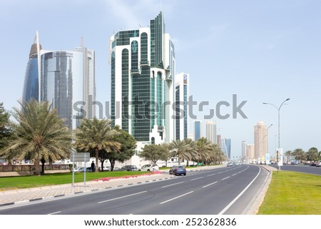 DOHA, Qatar - February 11, 2015: The Corniche road with the Public Works Authority, Salaam Tower and Doha Bank tower. - stock photo