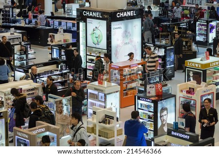 DOHA, QATAR - FEBRUARY 18, 2014: Tourists shopping at Duty Free Shop at Doha International Airport, the only commercial airport in Qatar. - stock photo