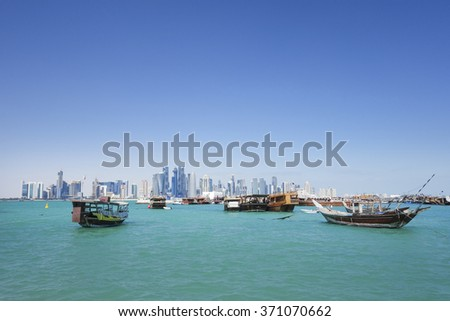 Doha, Qatar - January 29, 2016: Dhows moored off Museum Park in central Doha, Arabia, with some of the buildings from the city's commercial port in the background