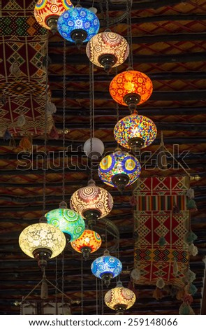 DOHA, QATAR - MARCH 8, 2015: Lanterns strung from the ceiling illuminate the Souq Waqif Arts Centre, with its hanging tapestries and traditional ceiling beams. - stock photo