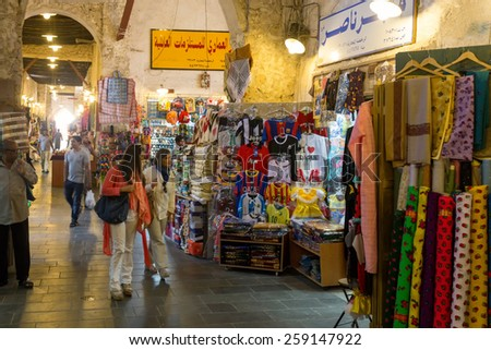 DOHA, QATAR - MARCH 8, 2015: Shoppers look at the goods in the covered part of Souq Waqif, a popular tourist attraction - stock photo